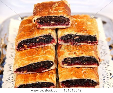 Strudel with poppy seeds and sour cherry on plate at rural retail market