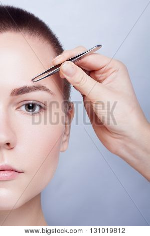 Young woman with short hair plucking eyebrows with tweezers close up studio snimak. on a light background. beauty shot. Closeup part of face woman plucking eyebrows depilating with tweezers.