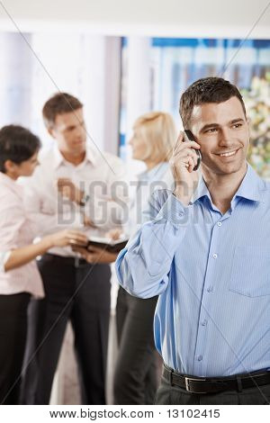Portrait of happy businessman talking on mobile phone in office.