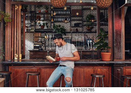 Portrait of trendy young man sitting at a cafe counter reading a book and drinking coffee