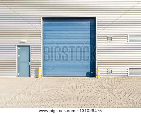industrial warehouse exterior with blue roller door