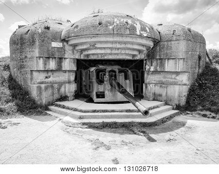 German defense battery against allied troops debarquement, bunker ruins with rusty gun, Longues sur Mer, Normandy, France. Black and white conversion.