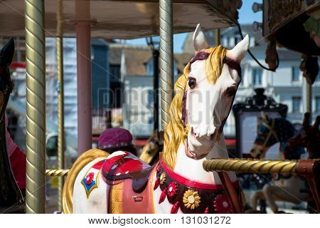 Bright carousel in a French village Honfleur. Horses on a traditional fairground vintage carousel