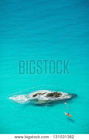 Small boat on the crystal clear sea near the town of Tropea, Calabria region - Italy and swimmers