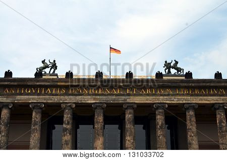 top of the old museum berlin with german flag