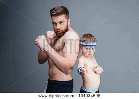 Portrait of athletic bearded father and his little son ready to fight over grey background
