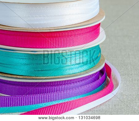 Set of grosgrain ribbons: blue violet crimson white. Background burlap. Colorful ribbons for craft and handmade sewing. Ribbons made from silk satin polyester. Burlap made from jute plant or sisal fibres. Reels made from carton. Four colors poster