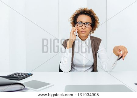 Beautiful african american young woman accountant sitting on workplace and talking on mobile phone