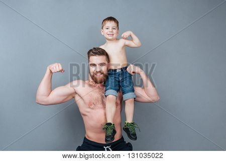 Handsome cheerful strong man holding his little son on his shoulder and showing biceps over grey background