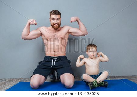 Cheerful handsome father and his little son sitting and showing biceps over grey background