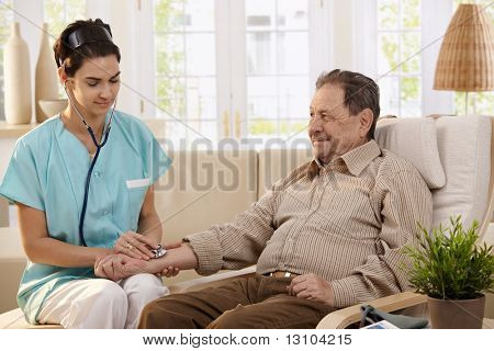 Nurse using stethoscope and measuring blood pressure of senior man at home.