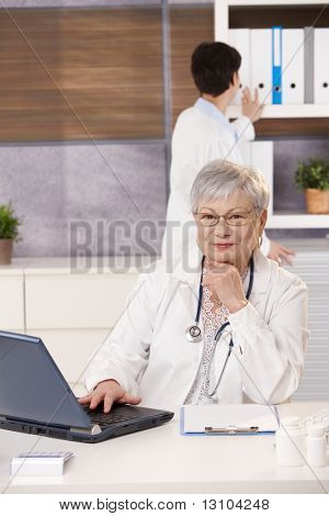 Smiling doctor sitting at desk with laptop, assistant looking at folder in background.