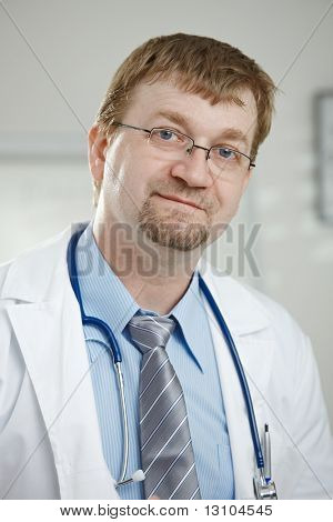 Medical office - portrait of middle-aged male doctor looking at camera.