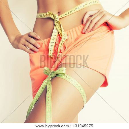 woman measuring waist with tape on knot like a gift, tann isolated close up white background good feat for summer
