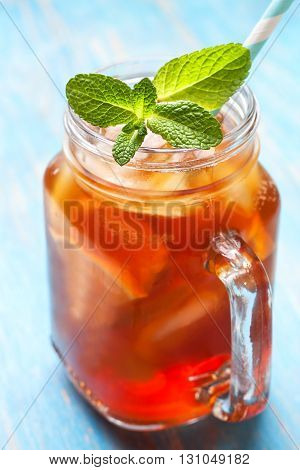 ice tea with mint and lemon in Mason jar on a blue background