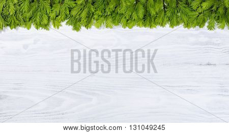 New fir tree tips on upper part of frame for Christmas or New Year border decoration on white wood. Plenty of copy space on lower part of image.