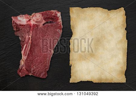 Delicious raw T-bone beef steak on black stone table, close-up.