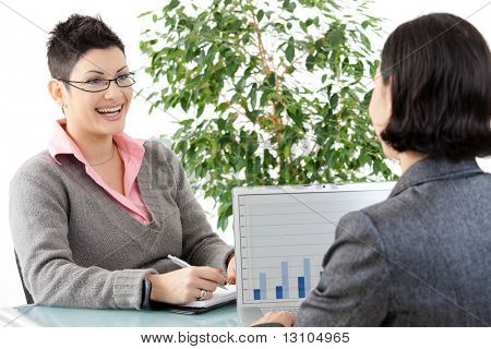 Young businesswomen having a business meeting, discussing business chatrs on laptop computer.