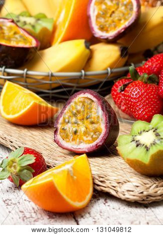 sliced passion fruit and tropical fruits in assortment: bananas kiwi strawberry mango pineapple