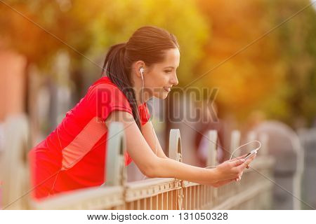 Young woman listening to music during sunny day in the city. Female fitness model training outside in Prague.