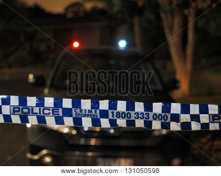 Melbourne, Australia -May 18, 2016: Blue and white Police tape cordoning off a car like an overnight crime scene