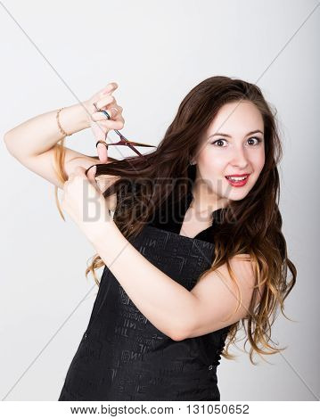 Very attractive and stylish professional hairdresser woman with scissors. hairdresser woman expresses different emotions and cuts himself bang.