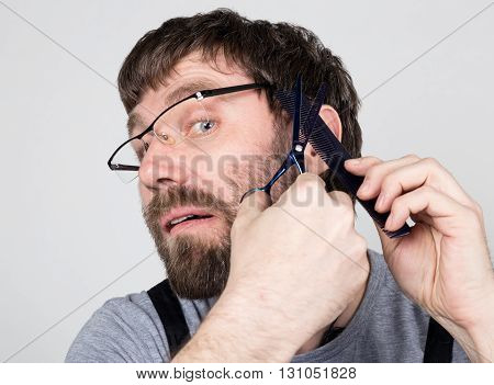 male barber cuts himself, looking at the camera like the mirror. stylish professional hairdresser expresses different emotions.