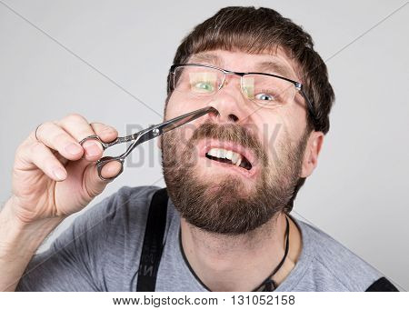 male barber cuts his own hair in the nose, looking at the camera like the mirror. stylish professional hairdresser expresses different emotions.