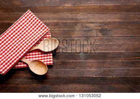 Checkered napkin and spoons on wooden background