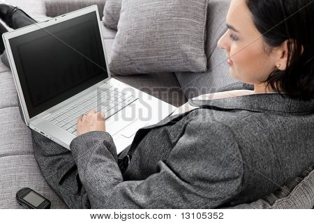Young businesswoman sitting on sofa, working with laptop computer. Isolated on white background, overhead view.