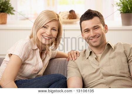 Smiling couple sitting on couch in sunny living room.