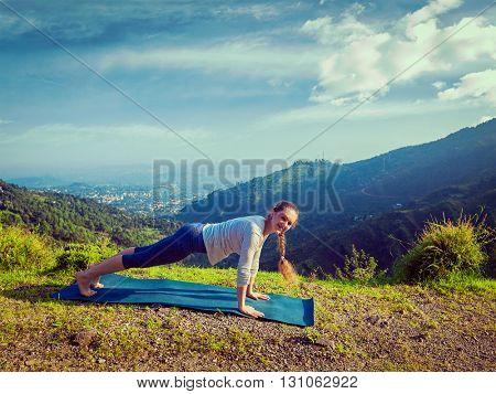 Vintage retro effect hipster style image of woman doing Hatha yoga asana Kumbhakasana plank pose  outdoors in mountains