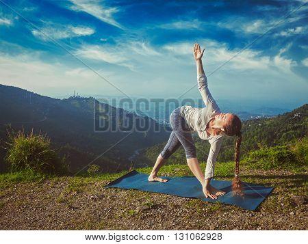 Vintage retro effect hipster style image of woman doing Ashtanga Vinyasa yoga asana Parivrtta trikonasana - revolved triangle pose outdoors in mountains in the morning