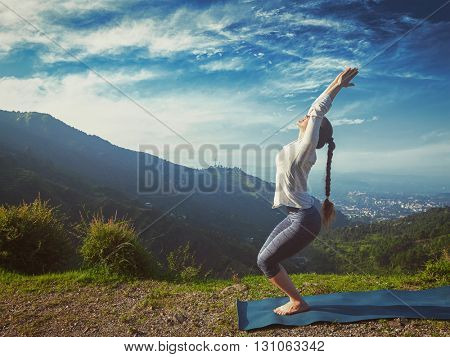 Vintage retro effect hipster style image of young sporty fit woman doing yoga asana Utkatasana (chair pose) outdoors in mountains Himalayas in the morning. Himachal Pradesh, India