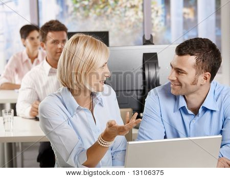 Young businesspeople sitting at desk, using computer talking at business seminar smiling.?