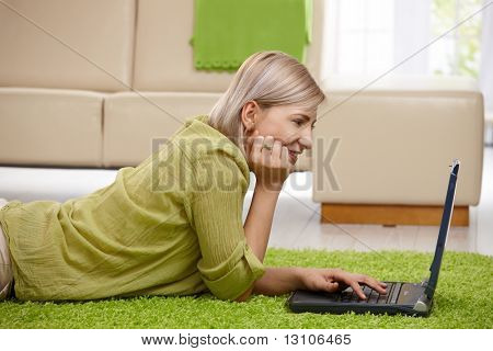 Smiling woman lying on floor at home looking at laptop screen, typing.?