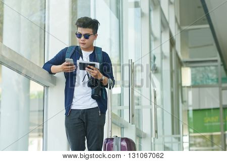 Asian traveler checking his phone when standing in terminal