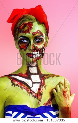 Portrait of a pin-up zombie woman over pink background. Body-painting project. Glamorous zombie girl. Halloween make-up.