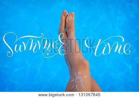 Feet on the background of the pool with words Summer time.