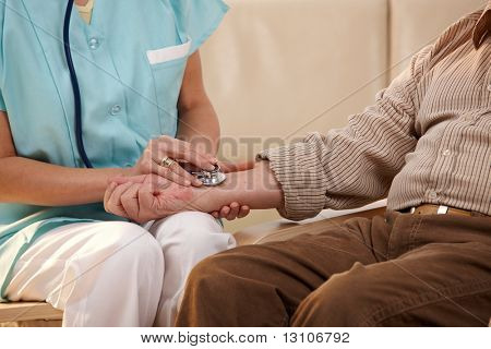 Closeup of nurse using stethoscope on wrist of senior man.