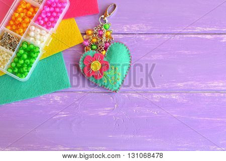 Bright hand felt keychain, felt sheets, organizer with wooden beads on a lilac background with empty copy space for text. Keychain crafts for kids, teens, preschoolers. Idea for arts, crafts project