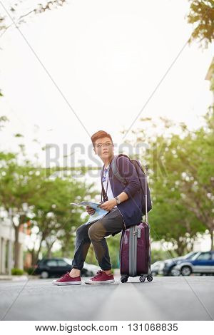 Vietnamese tourist sitting on suitcase with a map