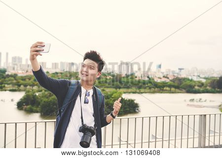 Young Asian man taking selfie on the background of big city