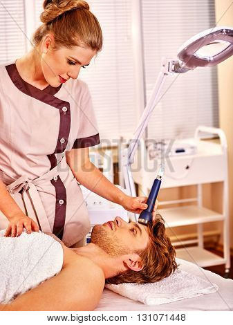 Young man luxuriating on electroporation  facial massage therapy at beauty salon. Man takes care of his face through facing massage. Used for  therapy of multifunctional electroporation  device. poster