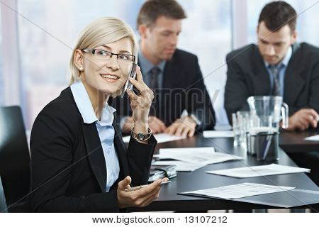 Successful businesswoman smiling talking on phone at meeting with businessmen in background.