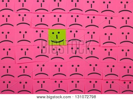 Happy and unhappy concept. Background of pink sticky notes. Happy sticky note is among unhappy sticky notes.