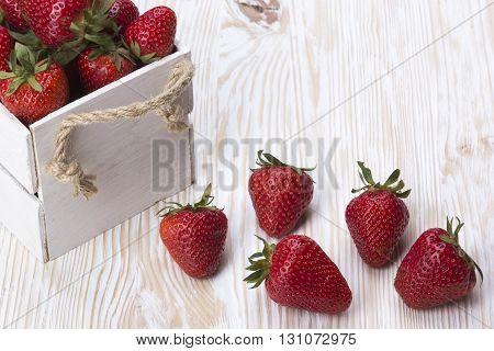 Strawberries in wooden box on wooden desk