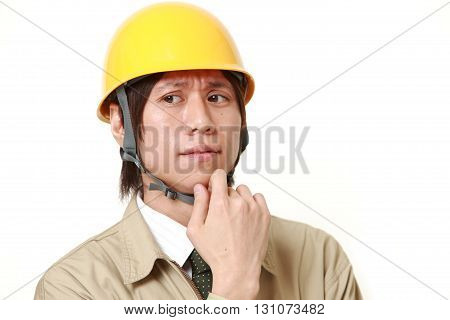 portrait of young Japanese construction worker worries about something on white background