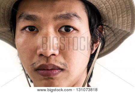 Close-up Asian guy in brown hat with serious face looking at camera