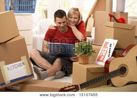 Happy couple looking at laptop computer together sitting in new house, surrounded with boxes.?